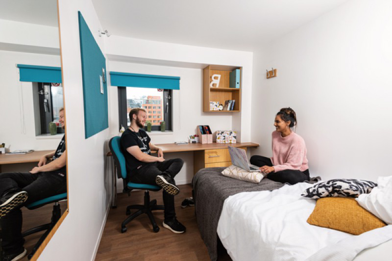 Two students chatting in a halls of residence room